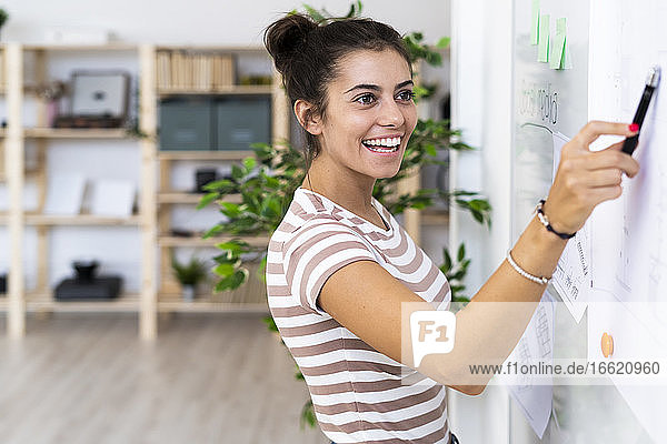 Happy female architect looking while pointing at whiteboard with felt tip pen at creative workplace