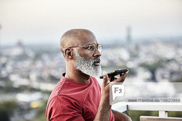 Bald man talking through smart phone while standing at building terrace during sunset