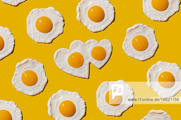Pattern of fried eggs against yellow background