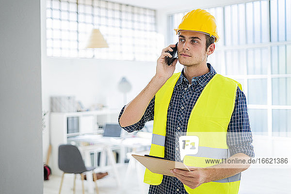 Young man talking on mobile phone while standing at office under construction