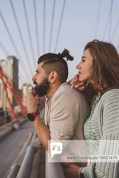 Thoughtful boyfriend and girlfriend looking away while standing on bridge in city