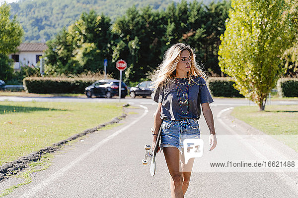 Beautiful young blond woman looking away while holding skateboard and walking on road in city during sunny day
