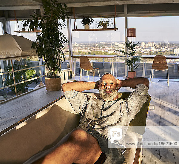 Relaxed mature man looking away while lying on sofa at building terrace during sunset