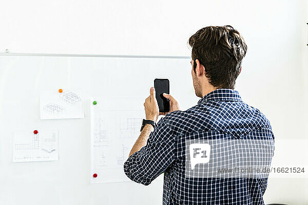 Young man taking photo of paper pin at whiteboard in office