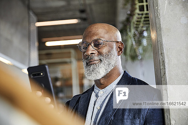 Smiling man text messaging on smart phone while standing at home