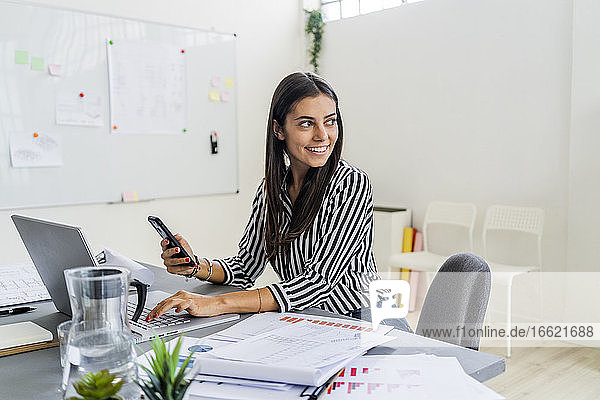 Happy female architect looking away while sitting with wireless technologies at desk in office