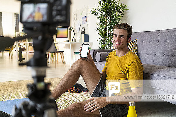 Smiling trainer showing mobile phone to camera while sitting at home