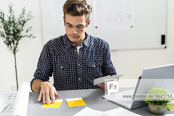 Man choosing yellow shade while sitting by desk at office