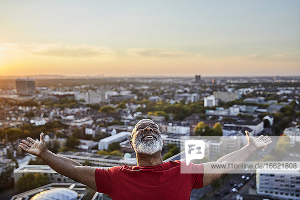Happy bearded man with arms outstretched while standing on building terrace in city during sunset