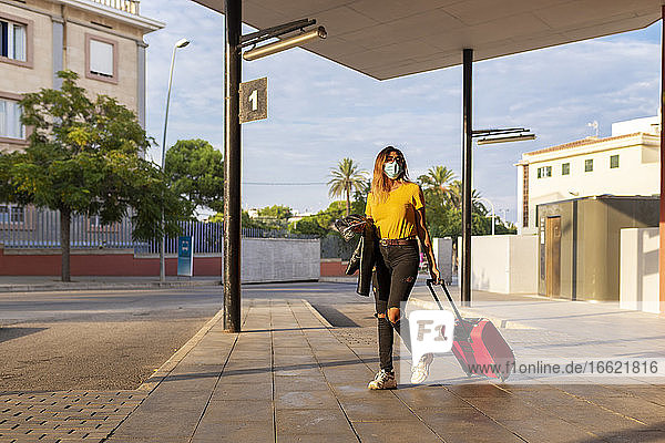 Young woman wearing protective mask while walking with luggage at bus stop