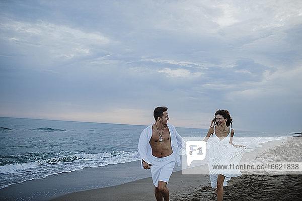 Lächelndes Paar  das sich beim Laufen am Strand ansieht