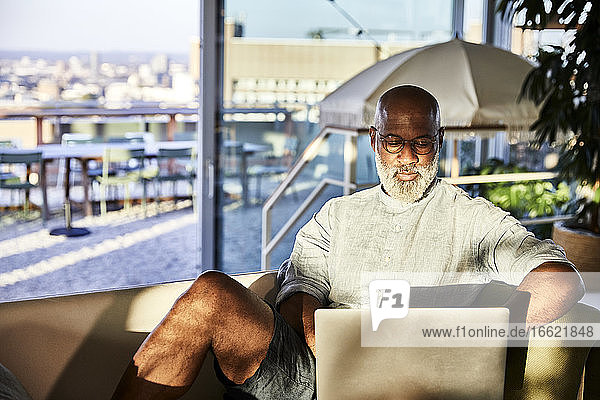 Mature man working from home while using laptop