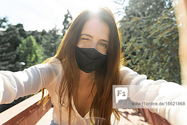 Woman wearing protective face mask taking selfie on sunny day