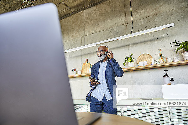 Mature man with headphone and digital tablet standing at home
