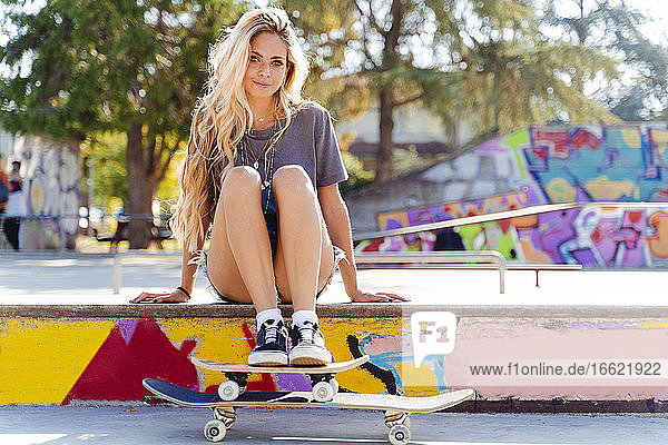 Beautiful blond woman sitting with skateboards at park