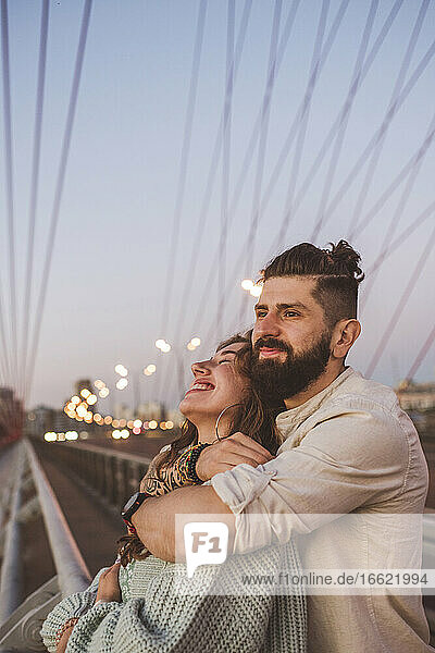 Boyfriend embracing happy girlfriend while standing on bridge in city