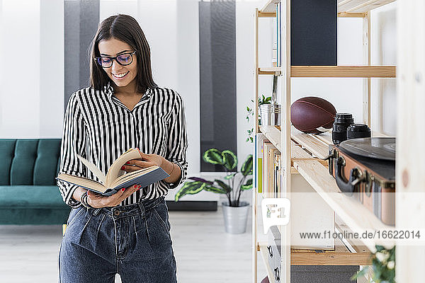 Smiling beautiful young businesswoman reading book while standing by rack at creative office