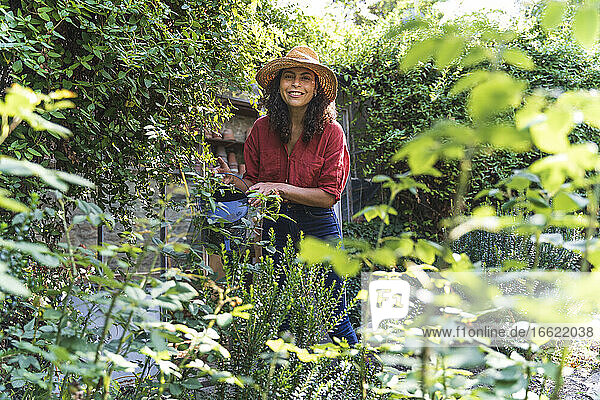 Mature woman wearing hat watering trees standing in back yard on sunny day
