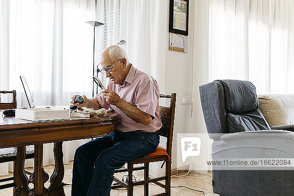 Retired elderly man using magnifying glass for research of fossil and mineral at home