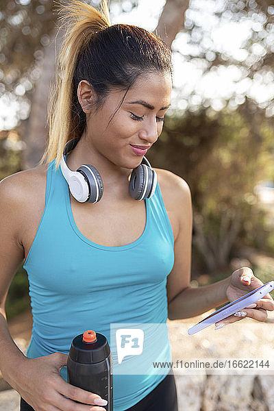 Smiling Hispanic woman using smart phone