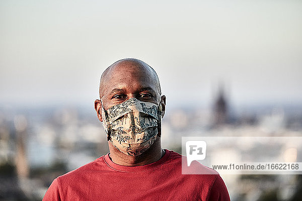 Bald man wearing protective face mask at rooftop against sky during COVID-19