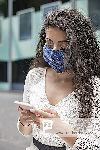 Close-up of young woman wearing face mask using mobile phone while standing in city
