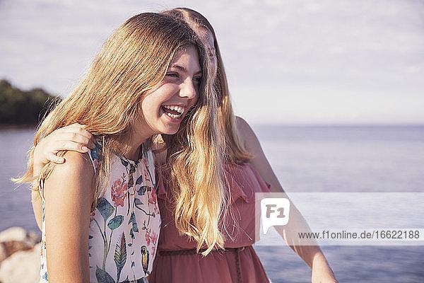 Blonde Mädchen lachen  während sie auf dem Bürgersteig während des sonnigen Tages stehen Blonde Mädchen lachen, während sie auf dem Bürgersteig während des sonnigen Tages stehen