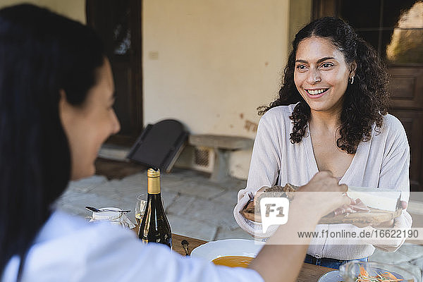 Woman giving bread to friend while having lunch at back yard