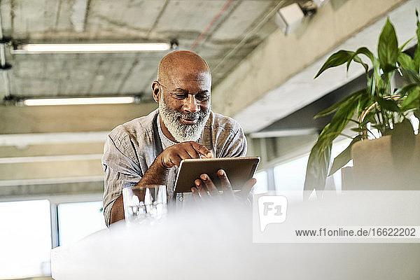 Smiling bald mature man using digital tablet at building terrace