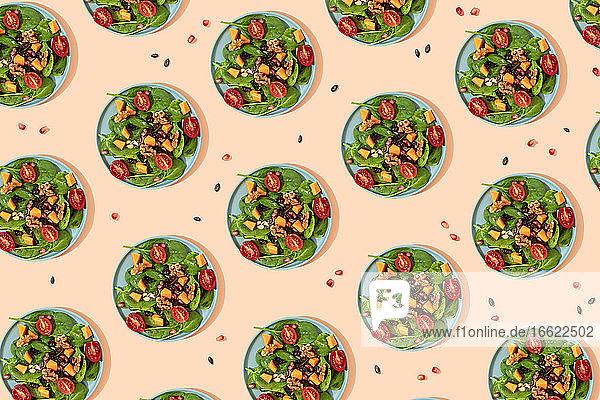 Pattern of plates of fresh ready-to-eat vegan salad