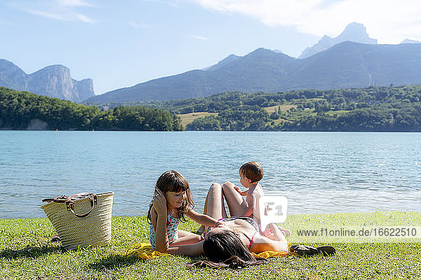 Daughters playing with mother on grass by lake