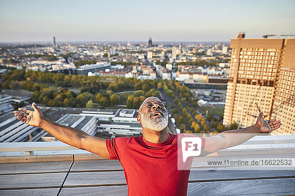 Happy bearded man with arms outstretched leaning back while standing on building terrace in city during sunset