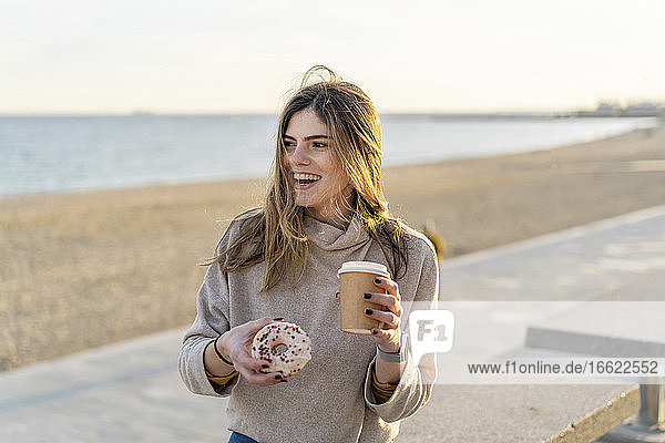 Cheerful woman holding fresh donut with disposable cup while sitting at beach and looking away against sky during sunset
