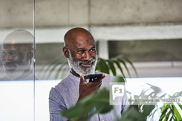Smiling mature businessman listening to call through smart phone while leaning on glass wall