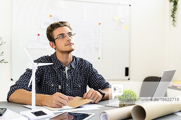Thoughtful man sitting by desk at office