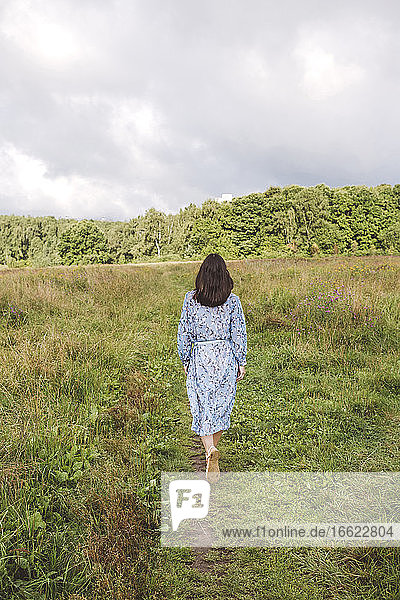 Mid adult woman walking on grassy land against cloudy sky