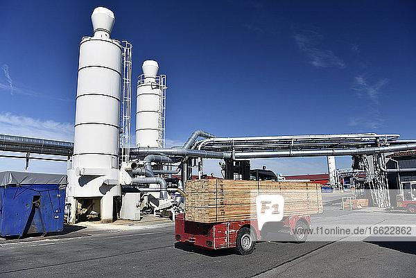 Forklift transporting planks in modern lumberyard
