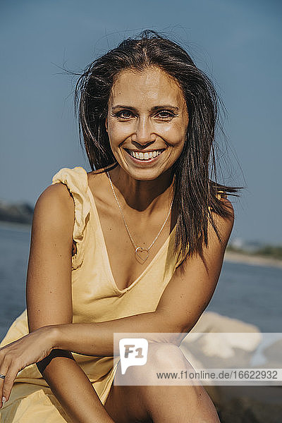 Smiling mature woman sitting on rock at beach