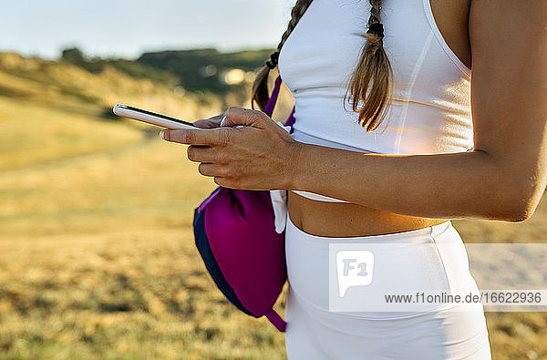 Close-up of young woman using smart phone while standing on land at sunset