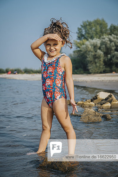Cute girl smiling while standing at beach on sunny day