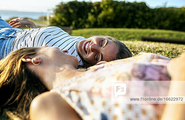 Happy young woman relaxing with sister on field during sunny day