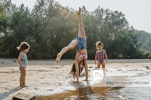Daughters watching mother cartwheeling at beach