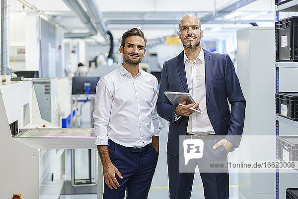 Confident mature businessman holding digital tablet while standing by young male engineer at factory
