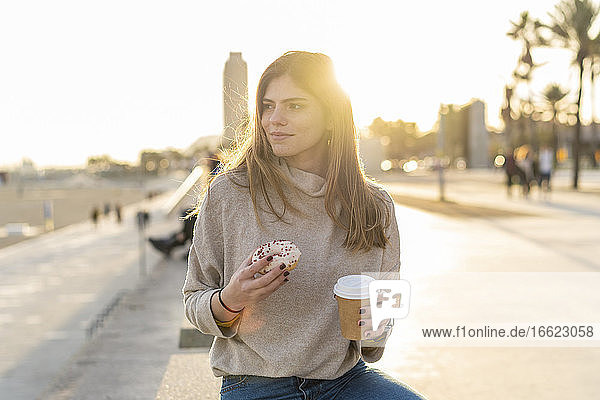 Thoughtful young woman holding fresh donut with disposable cup while sitting at promenade and looking away during sunset