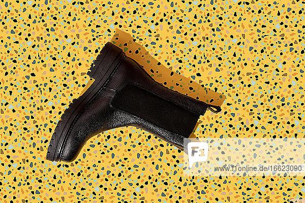 Black leather boot on yellow terrazzo pattern