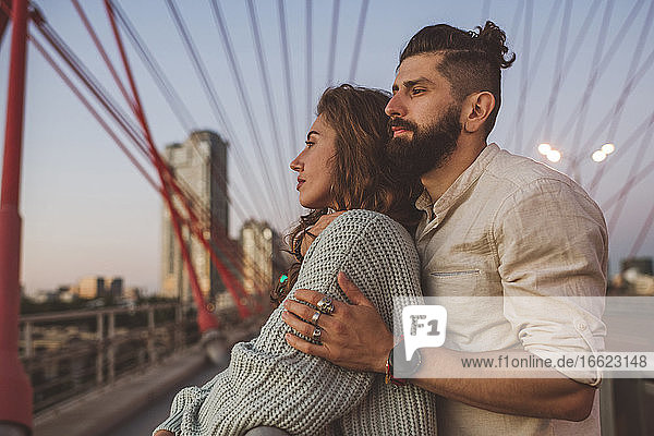 Contemplated couple looking away while standing on bridge in city during sunset