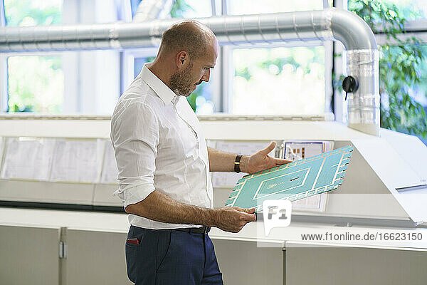 Confident mature male engineer examining large circuit board by machinery at factory