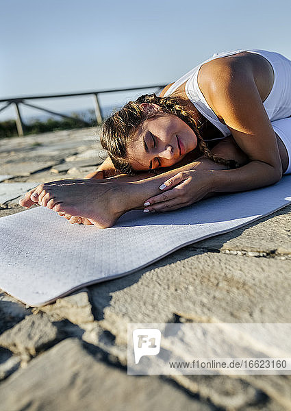 Young woman with eyes closed exercising on mat against clear sky during sunset