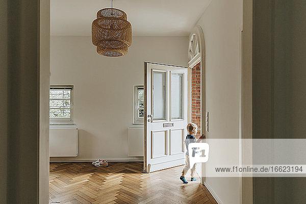 Boy standing by open door at home