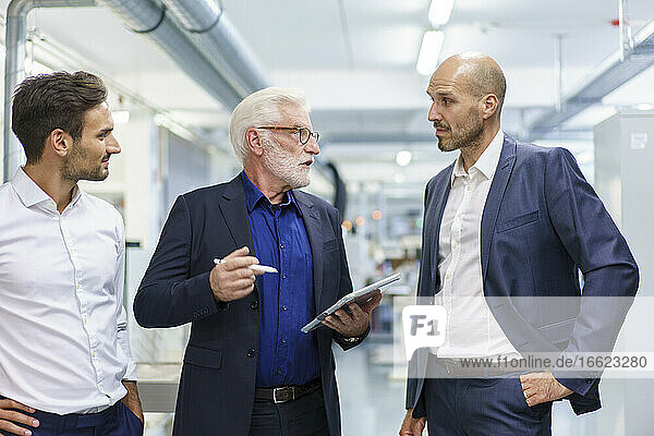 Senior male manager with colleagues discussing over digital tablet while standing at illuminated factory
